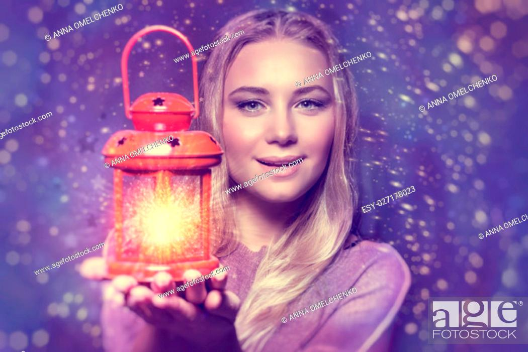 Stock Photo: Portrait of a beautiful woman holding on hand red retro style glowing lantern over night starry sky background, magical Christmas fairytale.