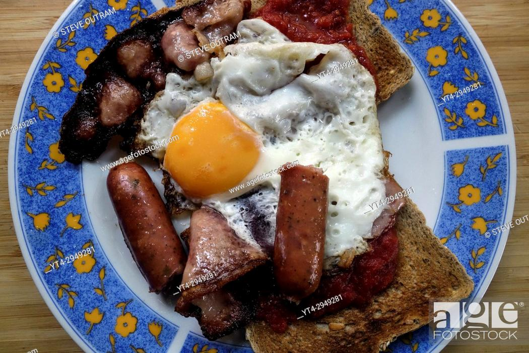 Stock Photo: Breakfast of Smoked Bacon, Sausages, Fried Egg and Brown Wholewheat Toast.