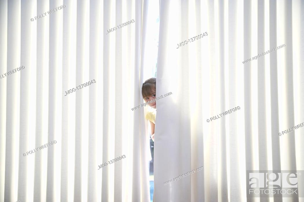 Stock Photo: Girl 5-6 peeking from behind blinds.