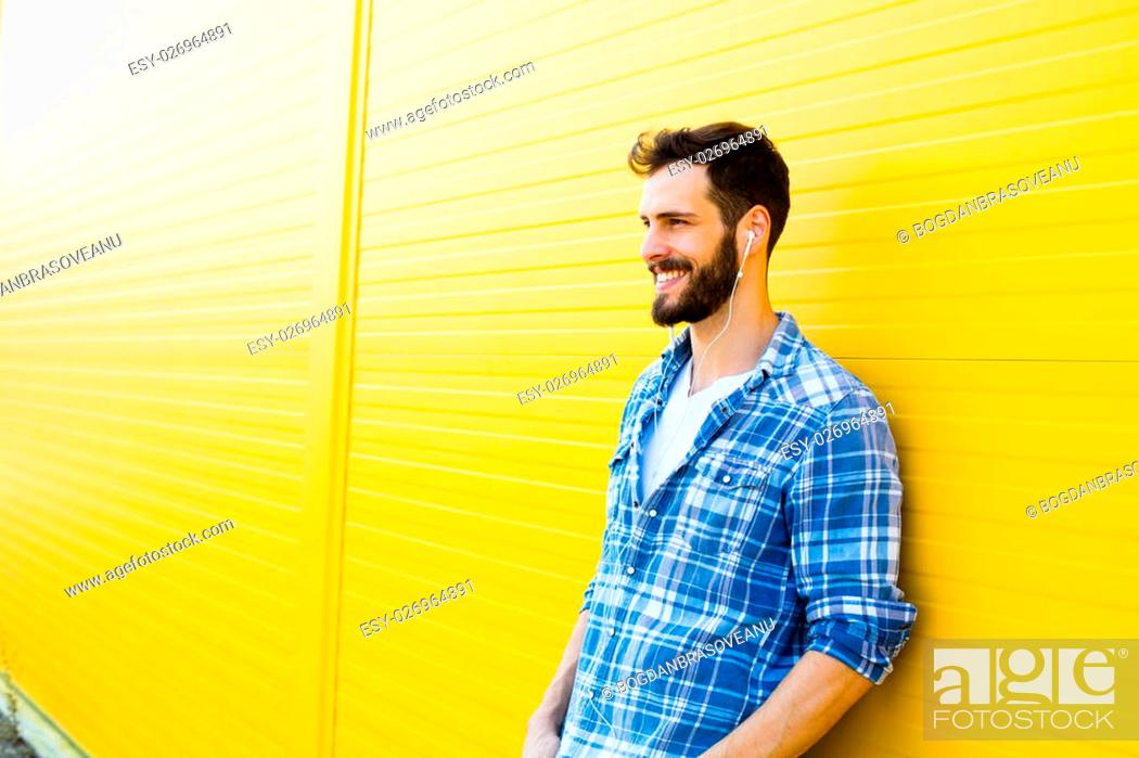 Young Happy Man Casual Dressed With Headphones And Smart