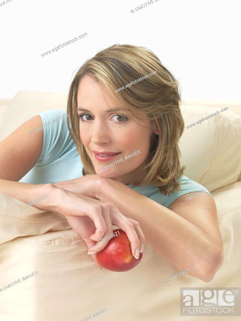 Stock Photo: Woman on the sofa with an apple.