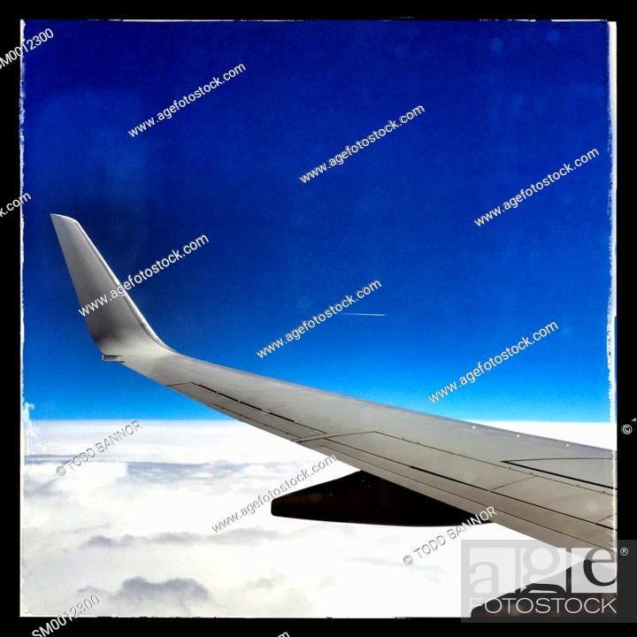 Stock Photo: Window view of airliner wing at 37, 000 feet.