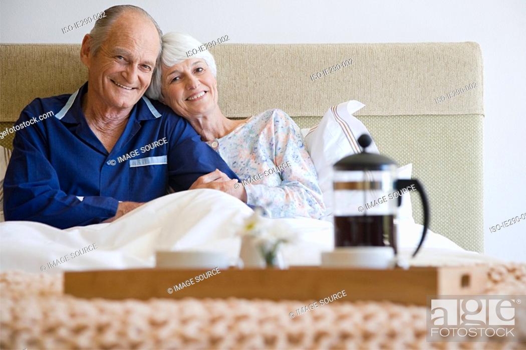 Stock Photo: Senior couple having breakfast in bed.