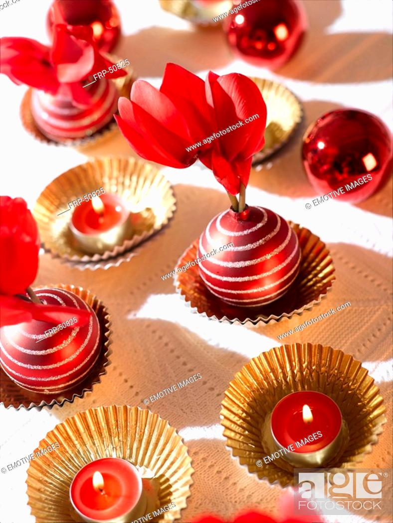 Stock Photo: Christmas table decoration with red candles, cyclamen and Christmas tree balls.