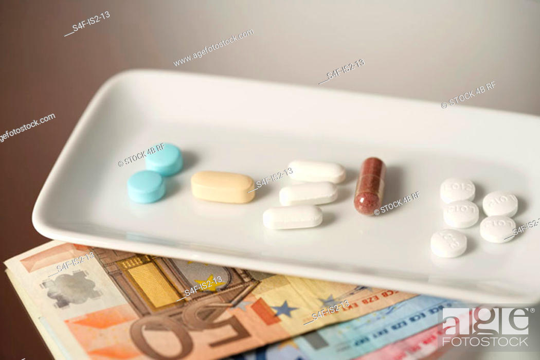 Stock Photo: Bowl with various pills on Euro-bills, close-up, high angle view.