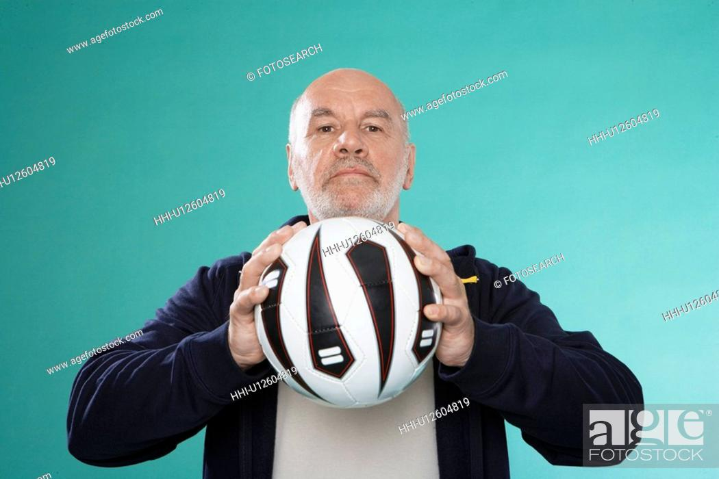 Stock Photo: Senior man holding soccer ball.