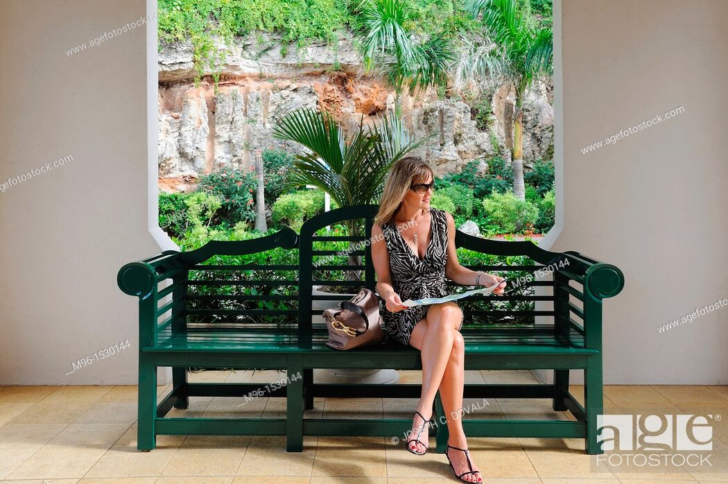 Stock Photo: Woman sitting on bench looking at map, Bermuda Island, Atlantic.