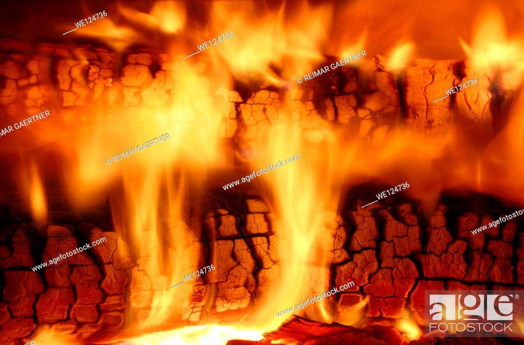 Stock Photo: Flames from burning wood logs in a high efficiency fireplace insert.