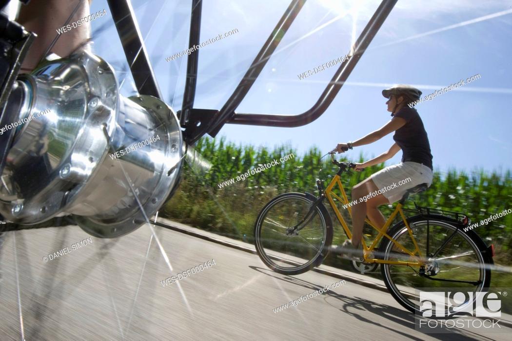 Stock Photo: Germany, Bavaria, Woman riding bicycle.