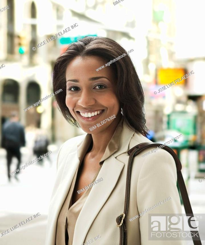 Stock Photo: Smiling African businesswoman on city street.