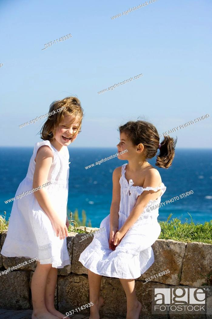 Stock Photo: Two caucasian girls in front of a blue sea.