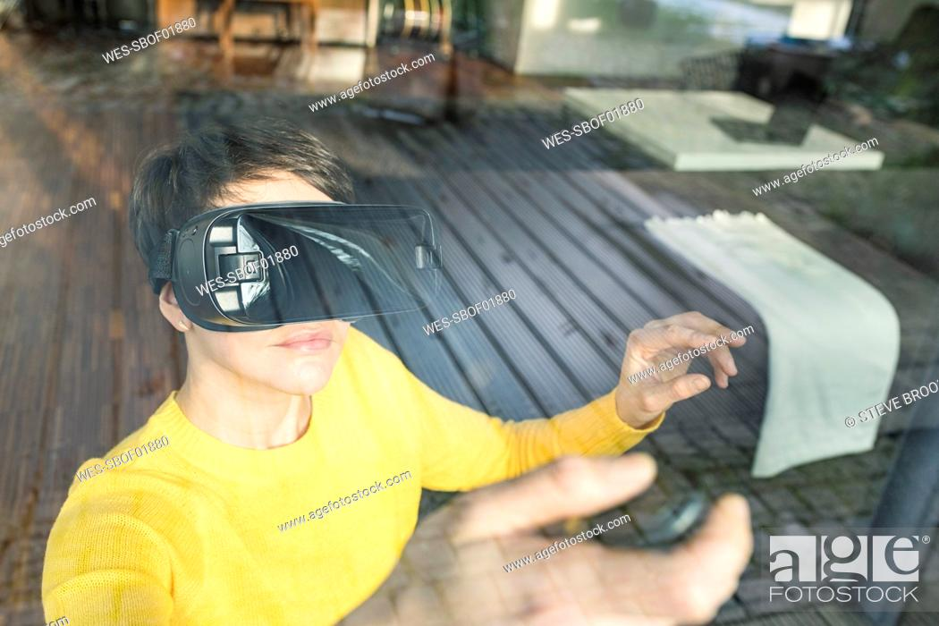 Stock Photo: Portrait of woman behind windowpane using Virtual Reality Glasses at home.
