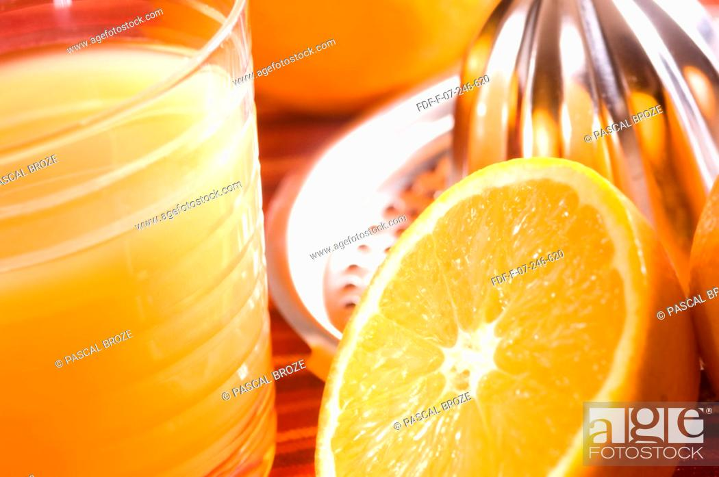 Stock Photo: Close-up of a juicer with an orange slice and a glass of orange juice.