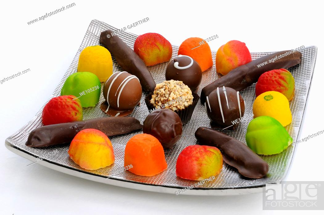 Stock Photo: Chocolate truffles candied orange rind and marzipan candies on a silver plate on white.