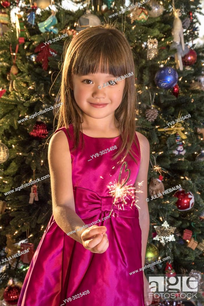 Stock Photo: Five year old girl holding a heart shaped sparkler at Christmas Eve.