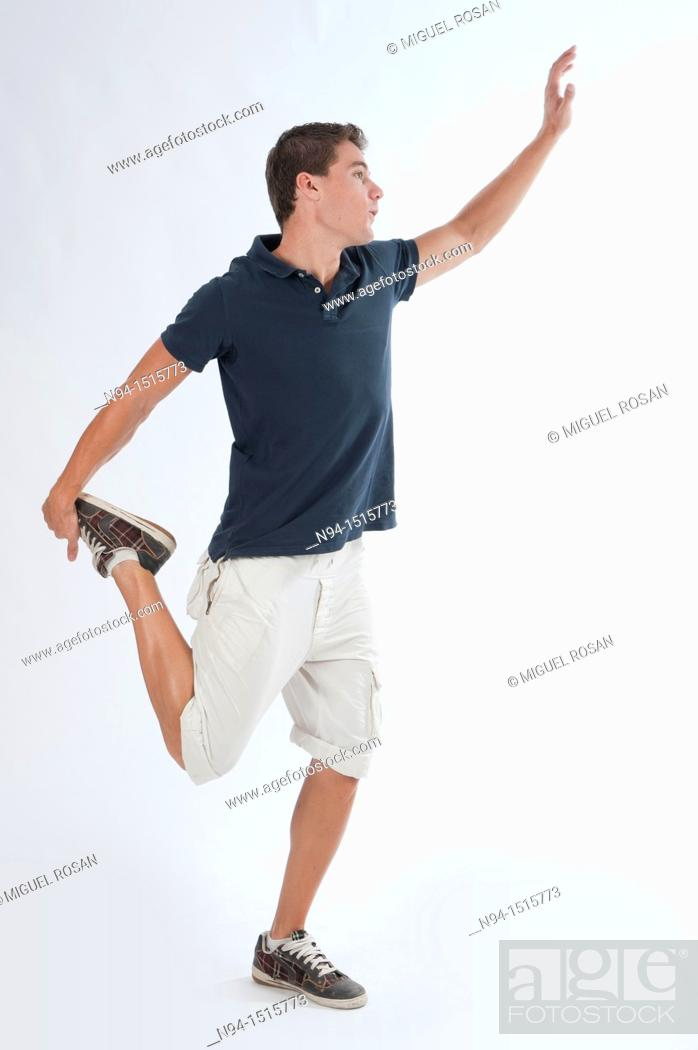 Stock Photo: Full-body photograph of a teenage boy standing with a jump or making a pirouette.