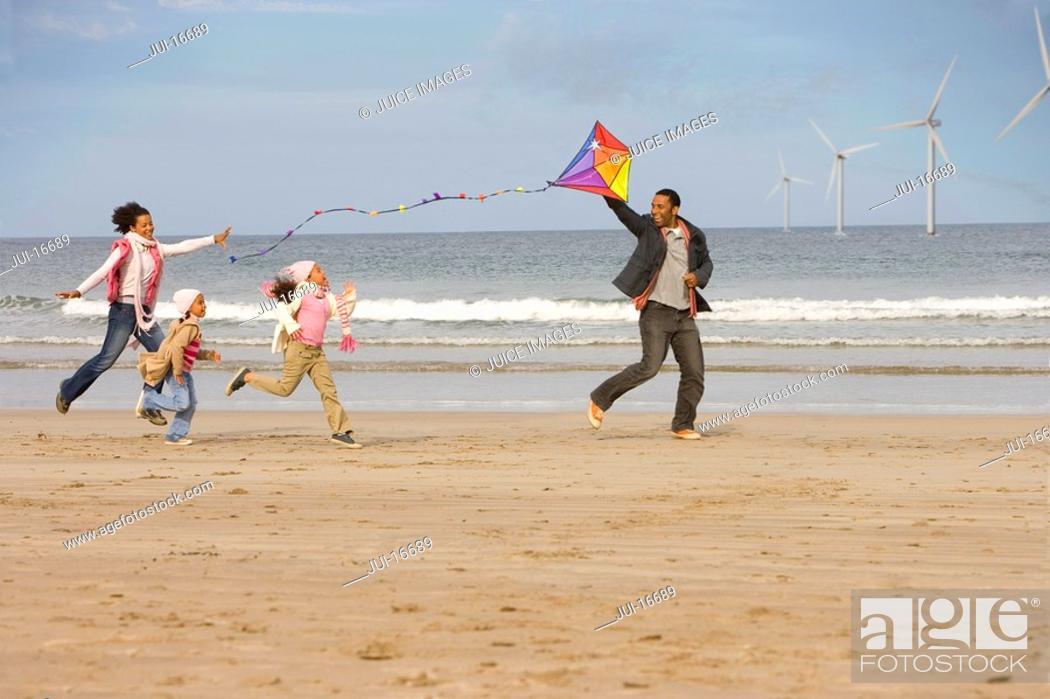 Stock Photo: Family running on beach with kite.