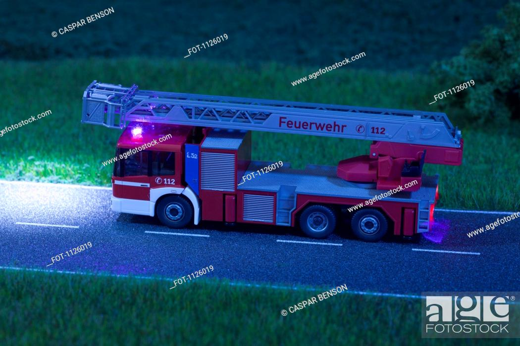 Stock Photo: A diorama of a miniature toy fire truck driving on a road at night.