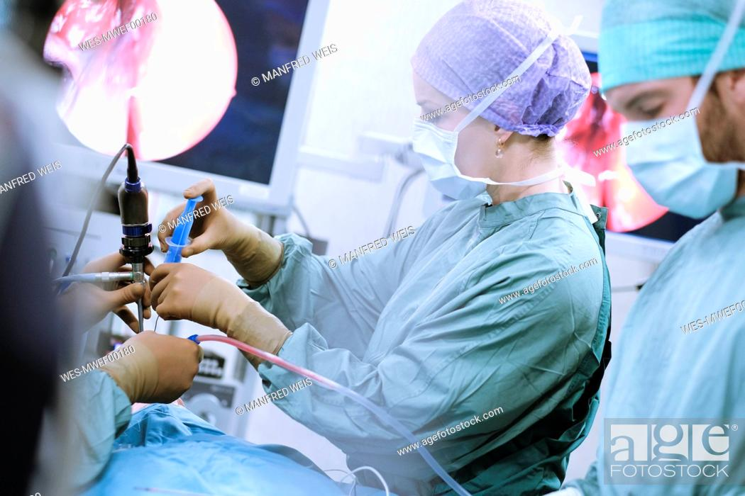 Stock Photo: Neurosurgeons in scrubs during an operation.