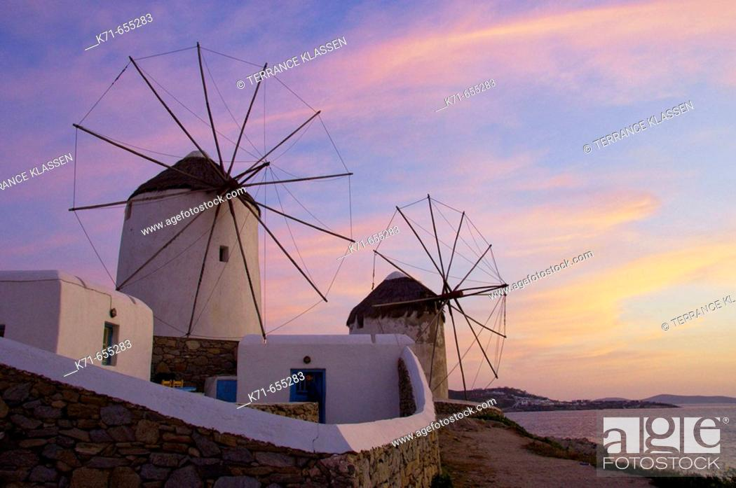 Stock Photo: The windmills of Mykonos at dusk and sunset up on a hill at Hora or Mykonos town, Greece.