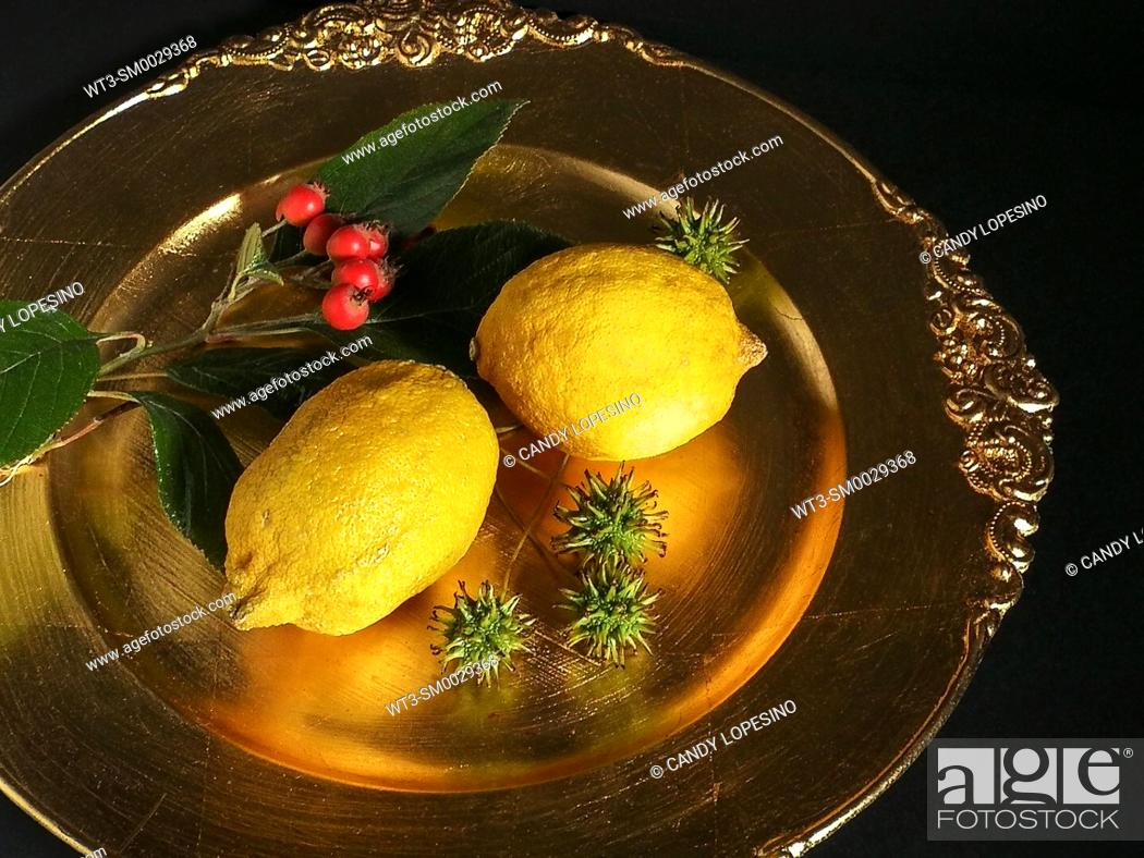Stock Photo: Two lemons on golden plate.