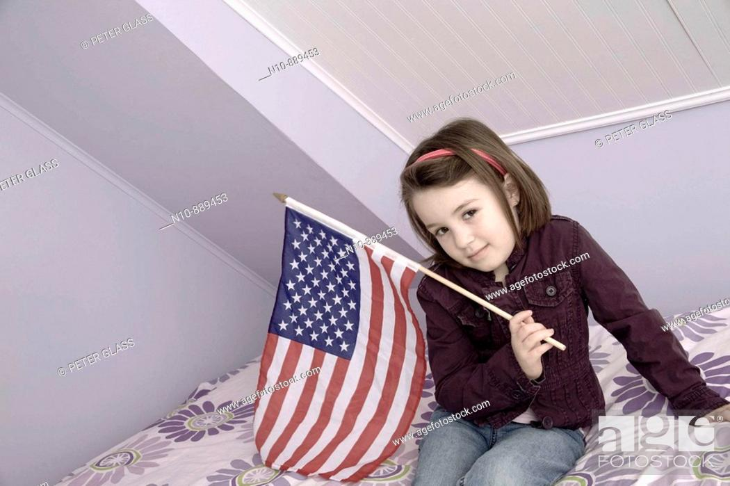 Stock Photo: Young girl holding an American flag.  Model and Property Released.