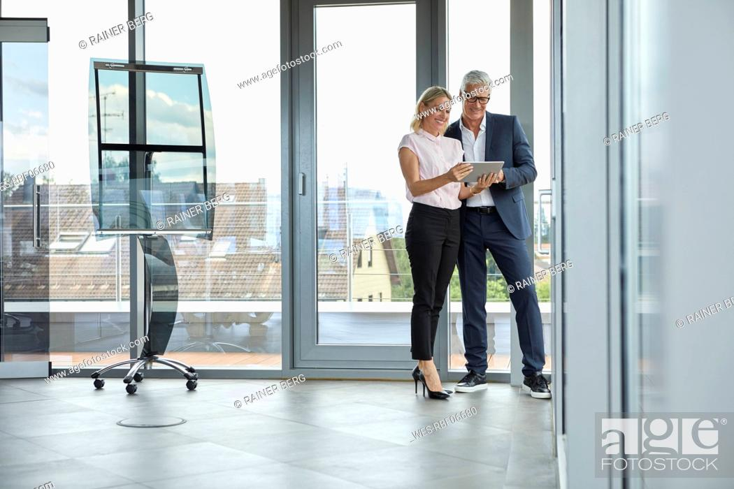 Stock Photo: Businessman and woman standing in office, discussing project, looking at digital tabet.