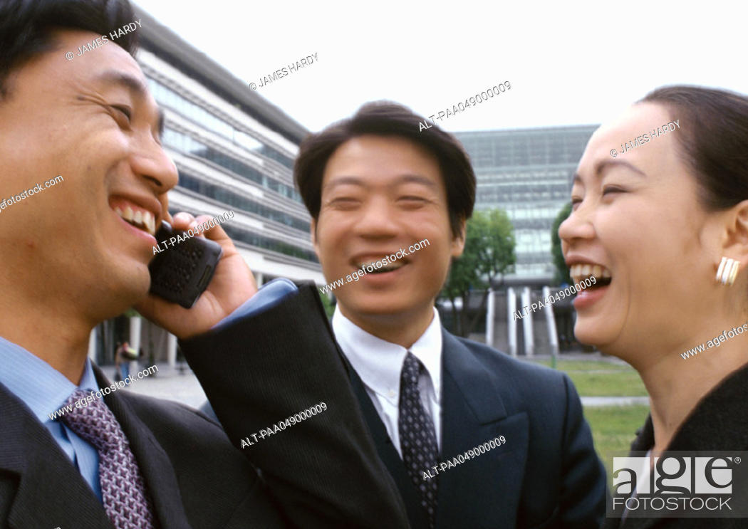 Stock Photo: Three businesspeople laughing, one holding cell phone.