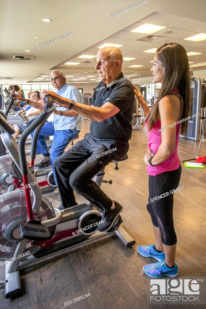 Stock Photo: Accompanied by his Asian American instructor, a healthy 92-year-old man works out on an exercise bicycle in the gymnasium of a senior center in Huntington Beach.