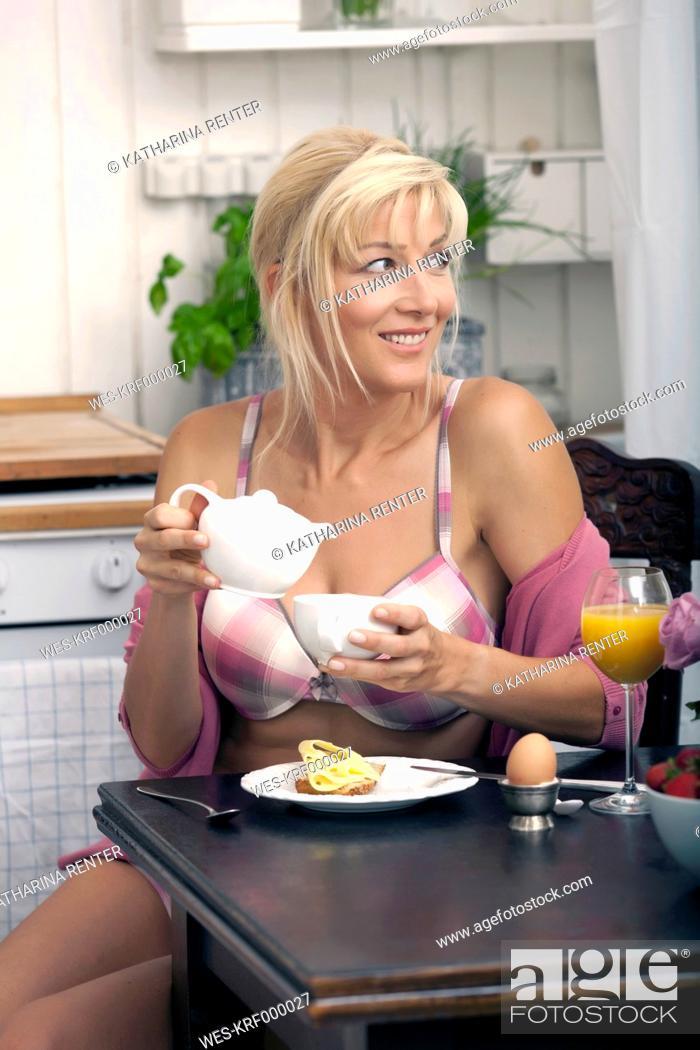 Stock Photo: Germany, Munich, Mature woman having breakfast in kitchen.