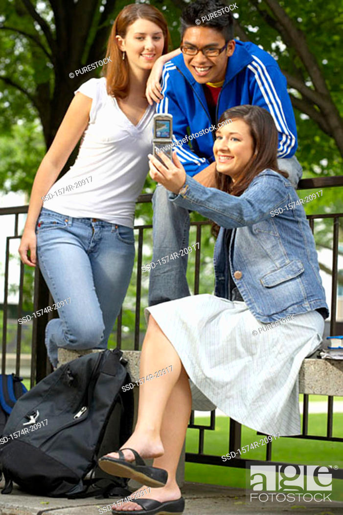 Stock Photo: Three college students taking their picture with a mobile phone.