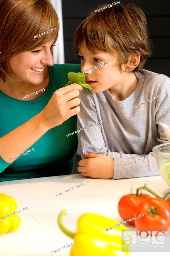 Stock Photo: Young woman feeding basil to her son.