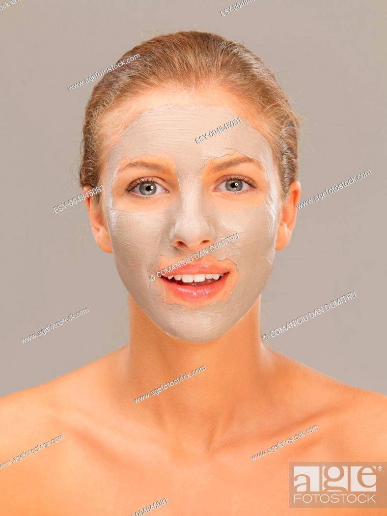 Stock Photo: beautiful woman with mud mask on face.