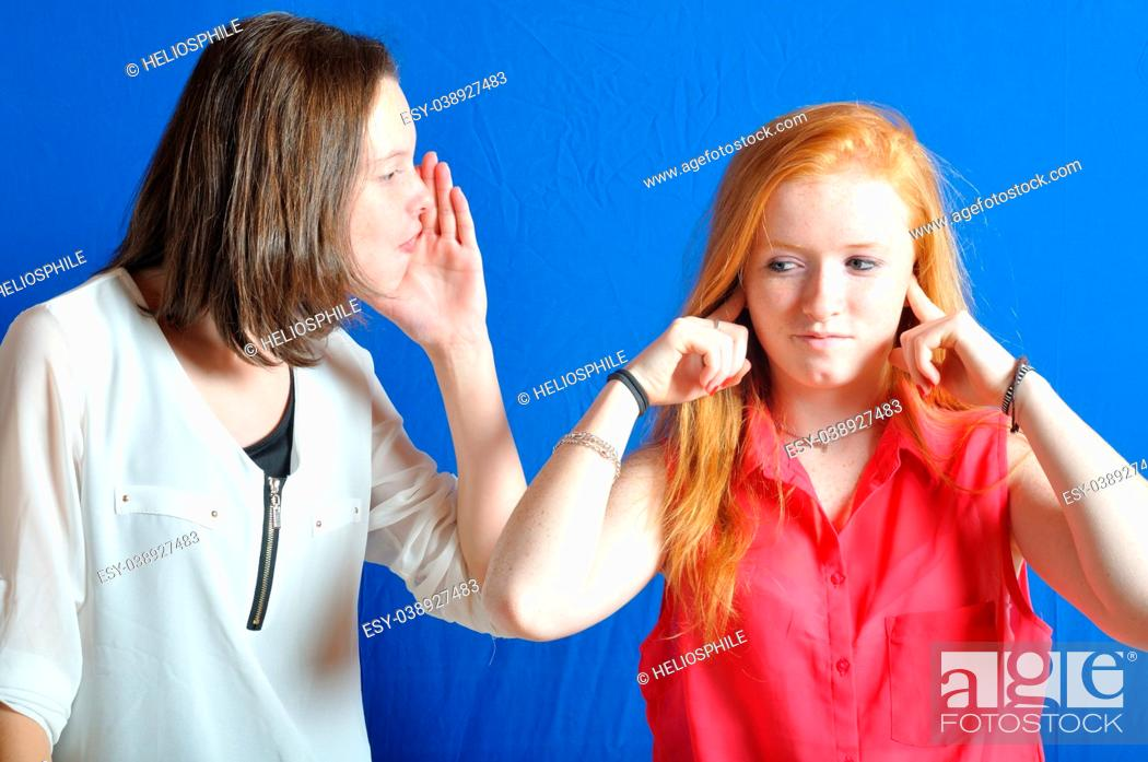 Stock Photo: Two teen, one shouting the other plug her ears.