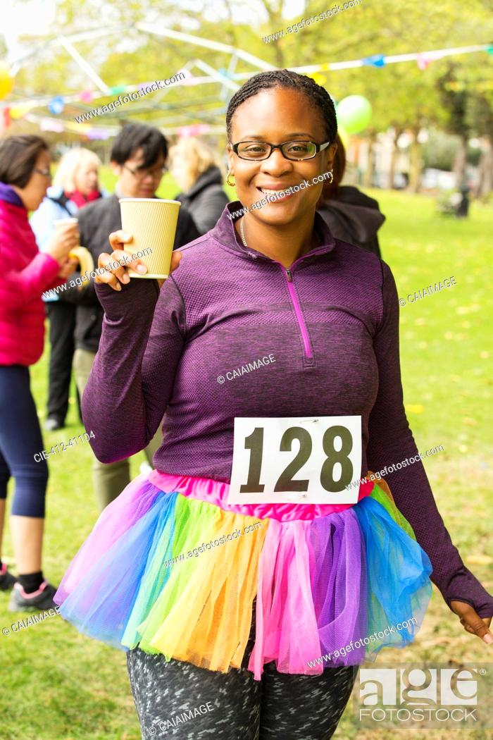 Stock Photo: Portrait smiling female runner in tutu drinking water at charity run in park.