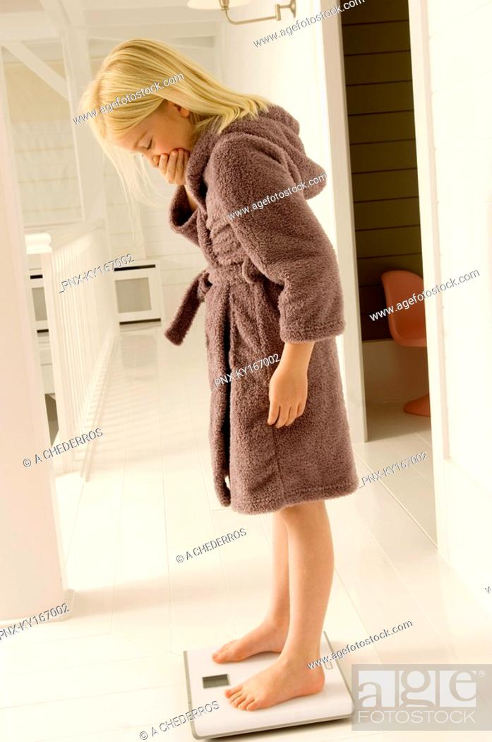Stock Photo: Girl standing on a weighing scale.
