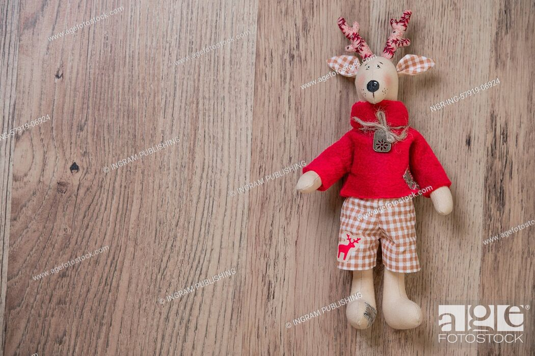Stock Photo: Handmade vintage Christmas deer on wooden background. Lots of copyspace.