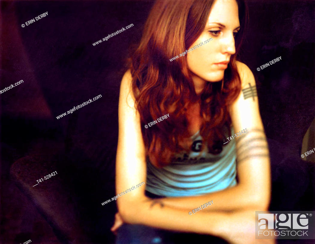 Stock Photo: A young woman pauses meditatively. She wears a CBGB's tank top and has many tattoos.