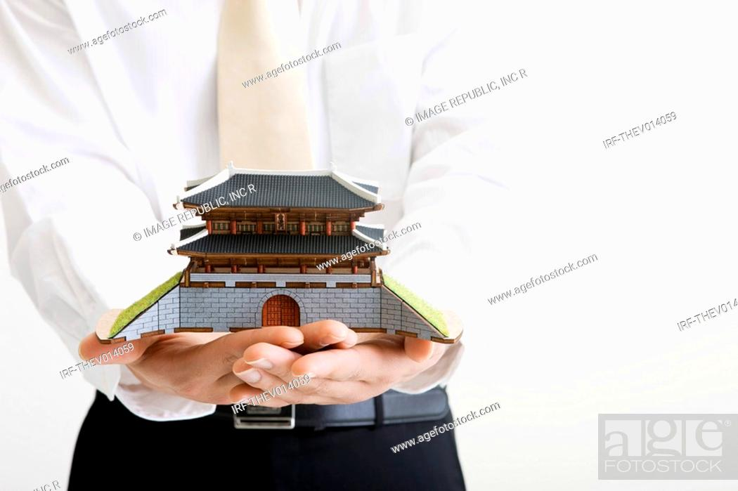 Stock Photo: businessman holding a Namdaemoon.