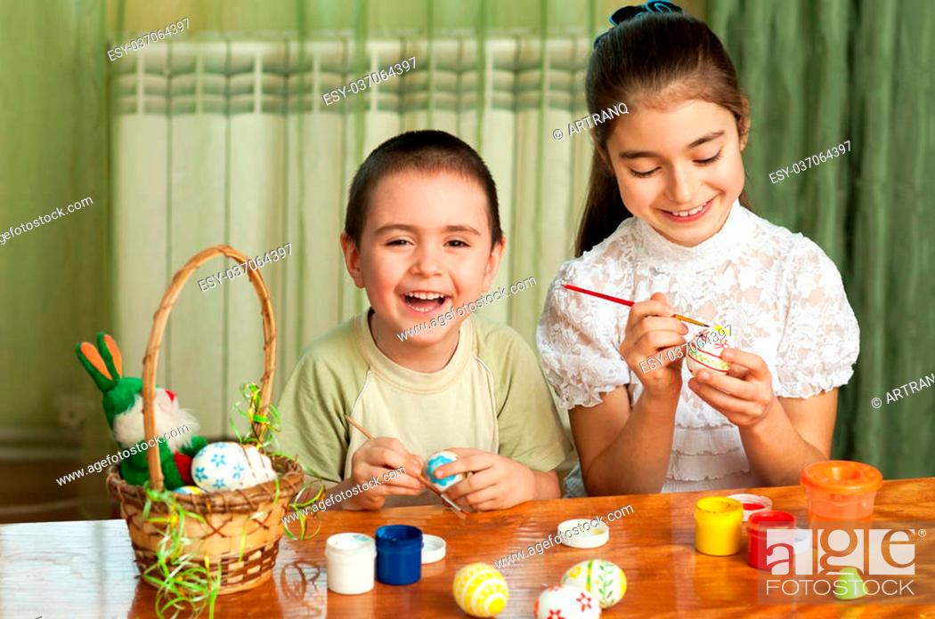 Stock Photo: brother and sister painted Easter eggs at the table.