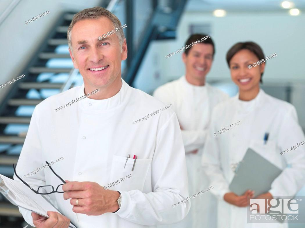 Stock Photo: Scientist carrying clipboard in office.
