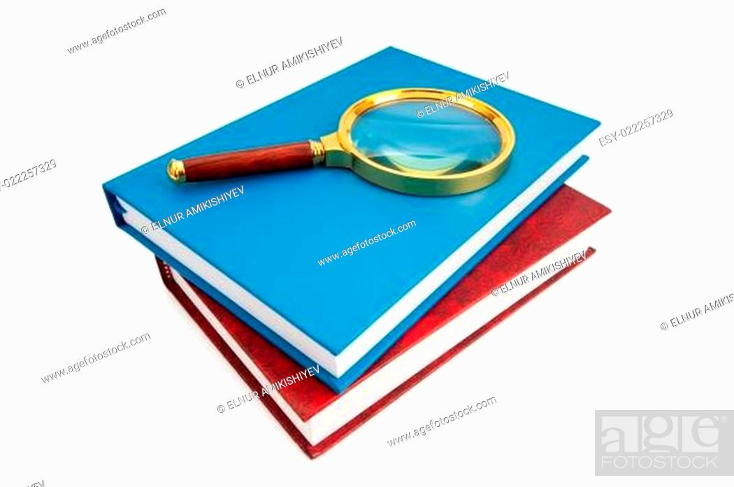 Stock Photo: Magnifying glass over the stack of books.