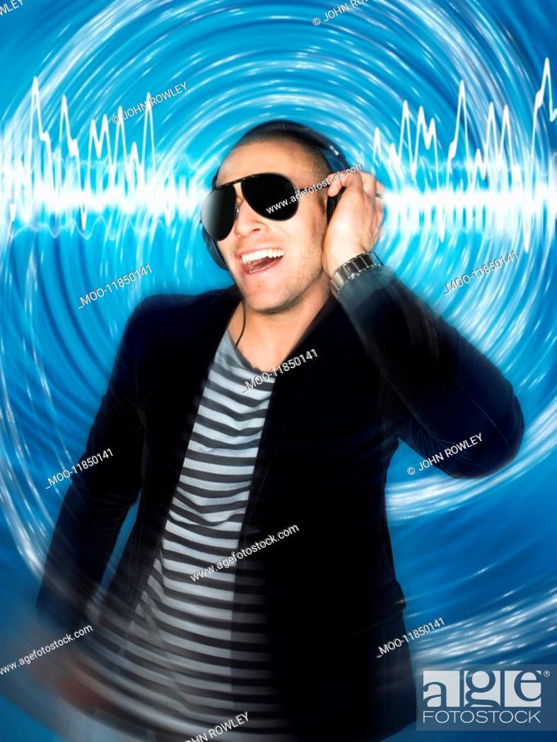 Stock Photo: Man wearing headphones in front of circular effect half-length.