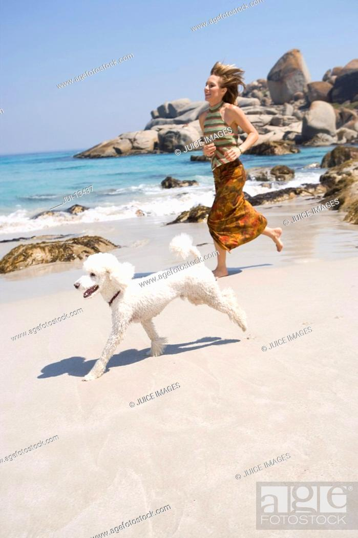 Stock Photo: Woman running with poodle on beach, smiling.