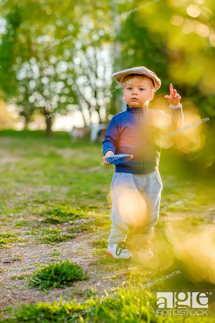 Stock Photo: Toddler child outdoors. Rural scene with one year old baby boy wearing flat cap.