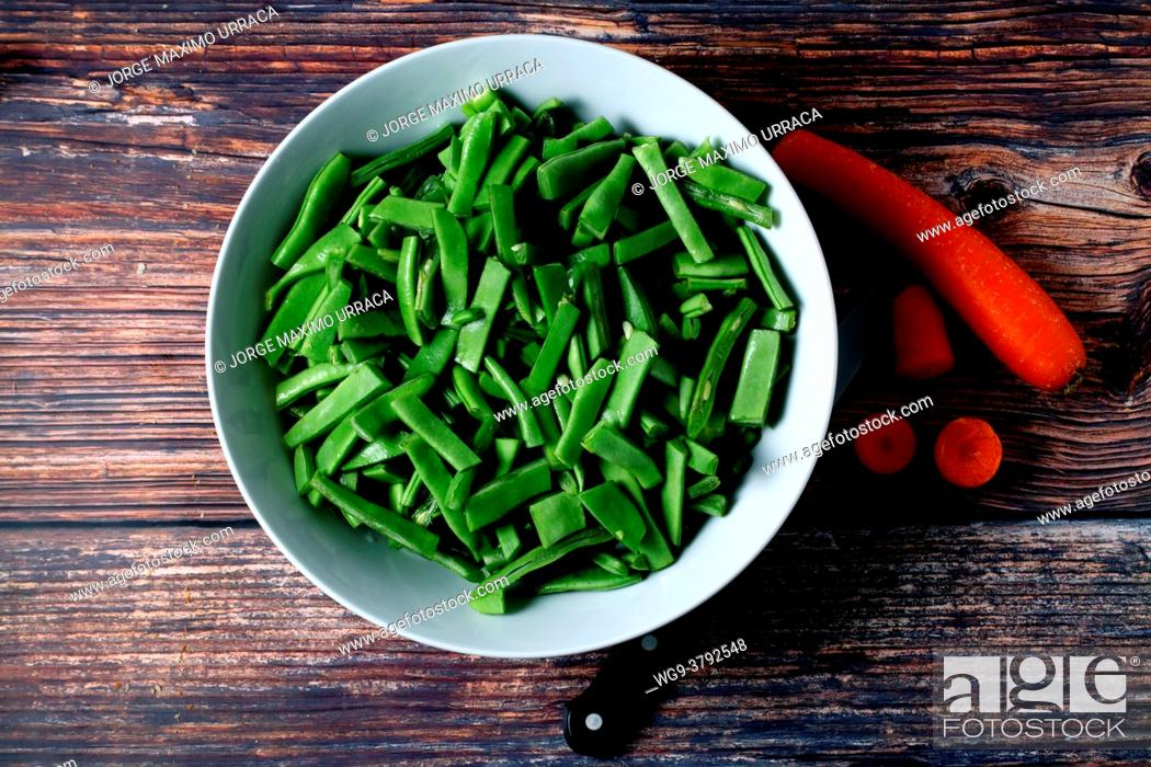 Stock Photo: Raw green beans in bowl on wooden board.