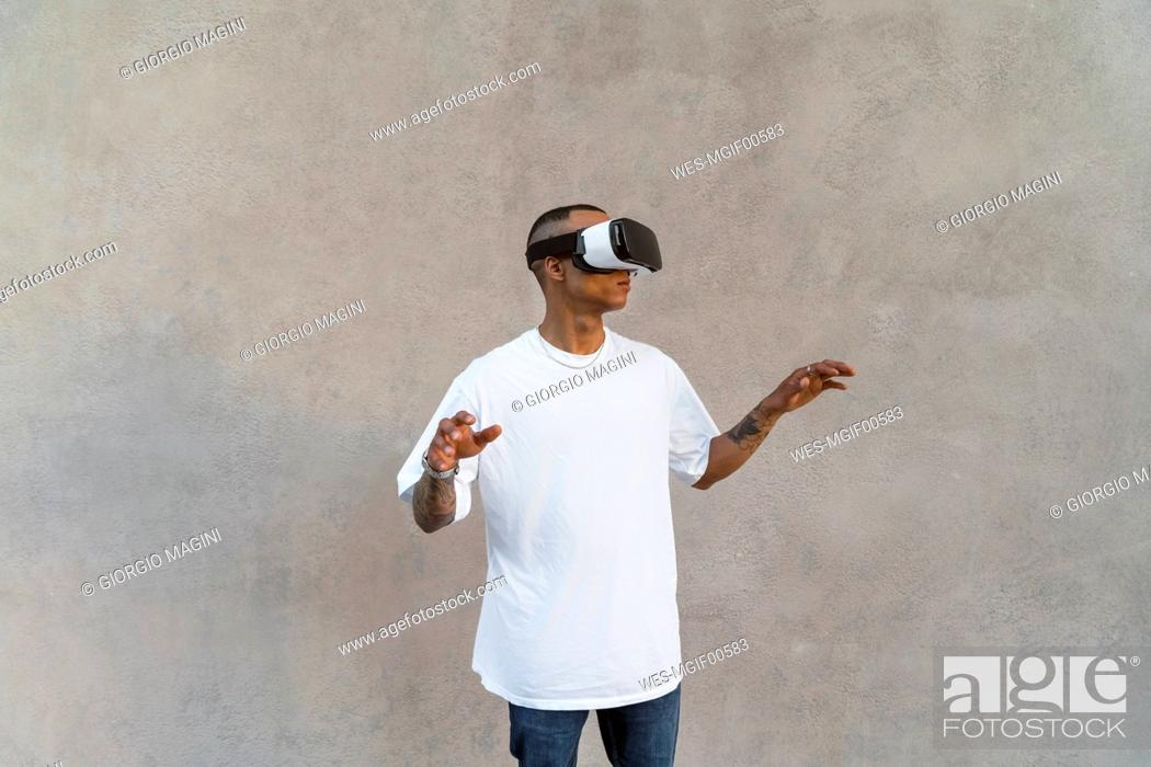 Stock Photo: Tattooed young man using Virtual Reality Glasses.