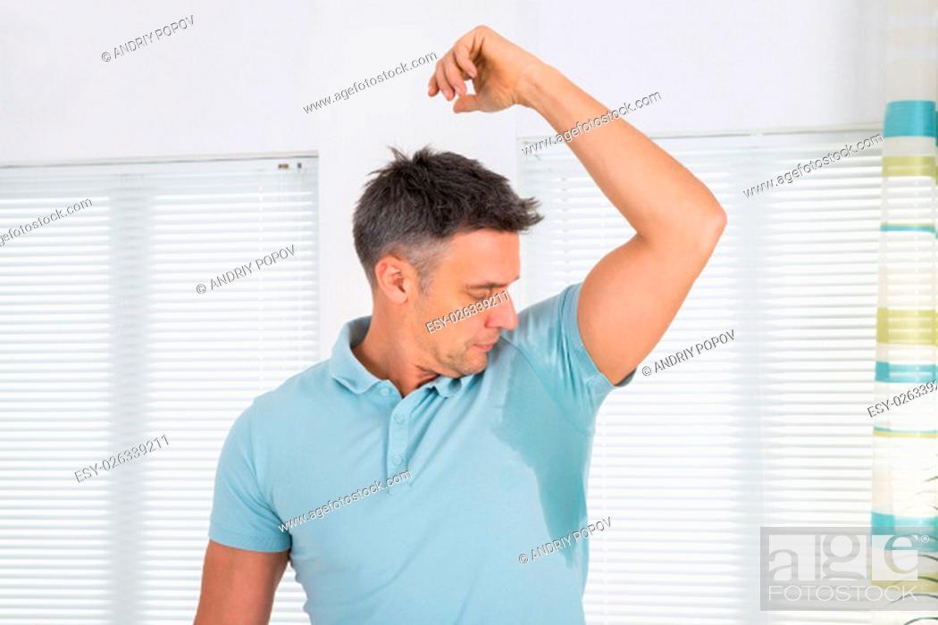 Stock Photo: Mature Man Notices His Sweat Under Armpit.