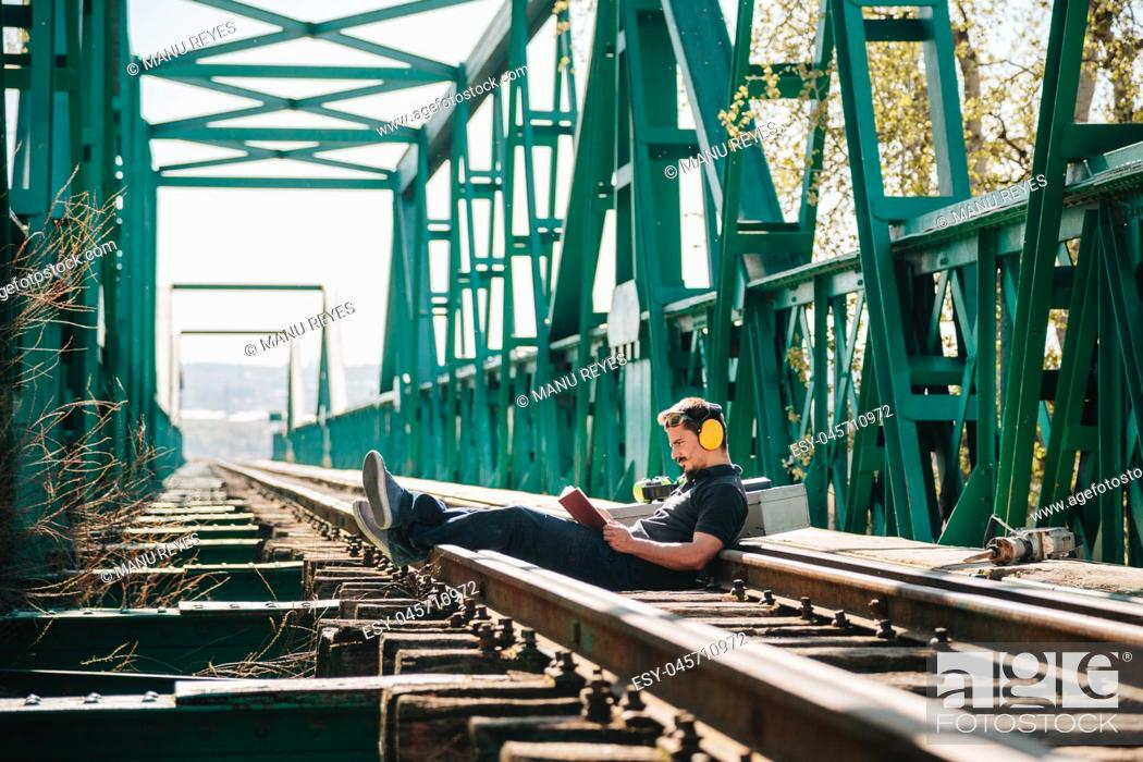 Stock Photo: Young construction worker man rests sitting reading a book on an old steel railway bridge.