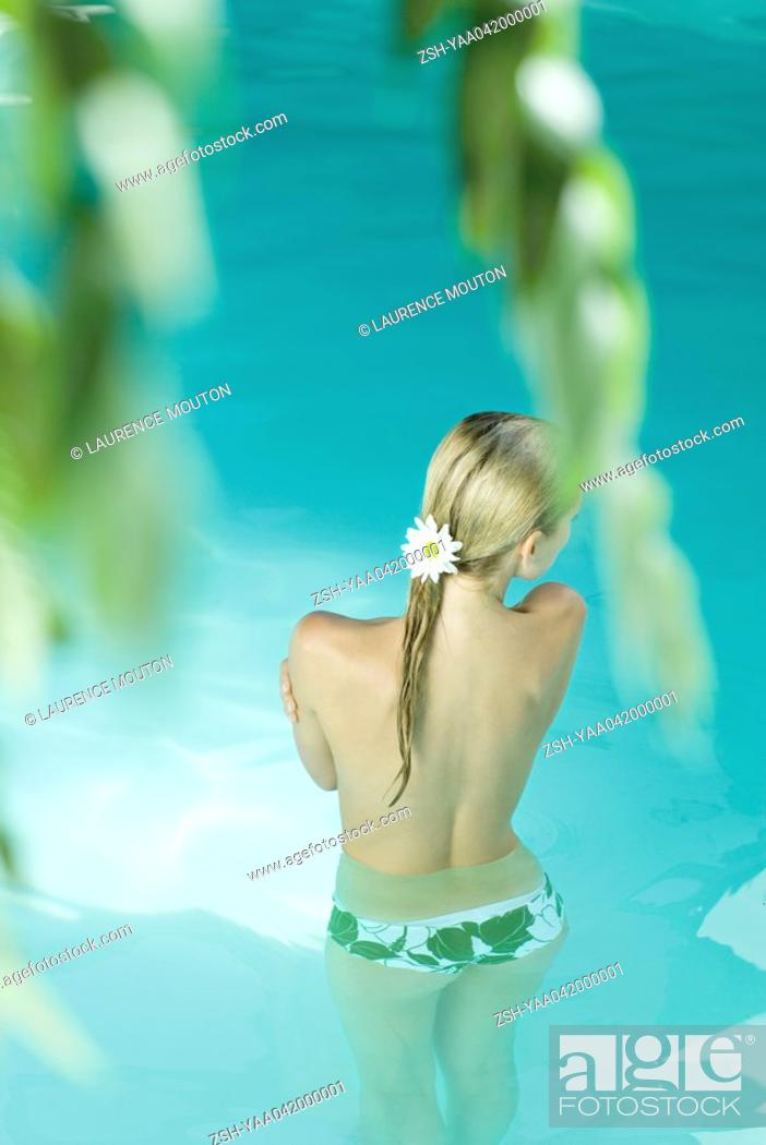 Stock Photo: Young woman standing waist deep in pool, rear view.